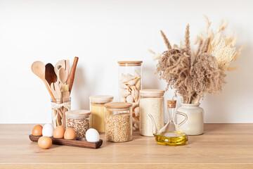 Assortment of cereals and pasta in glass jars and woden kitchen utensils. Zero waste idea