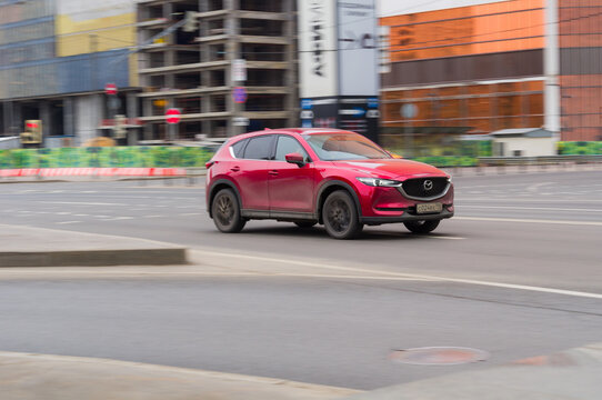 red Mazda CX-5 on the city street. Fast moving SUV on urban road with blurred background