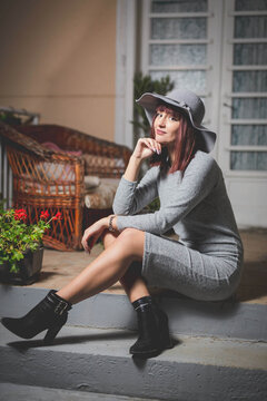 Caucasian woman in a gray hat and black tall boots posing on stairs leading to front door of house