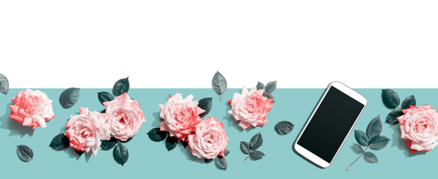 Smartphone with pink roses overhead view