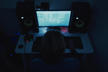 Fototapeta Shallow focus of an adult producer composing music with a computer in a dark room obraz