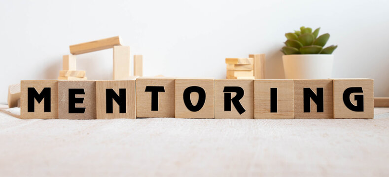 Mentoring - word from wooden blocks with letters, help and advice mentoring concept.