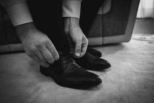 Grayscale shot of a man tying his leather shoes