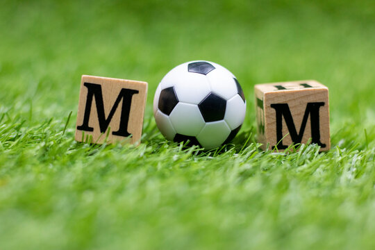 Soccer ball with word mom are on green grass for mother's day