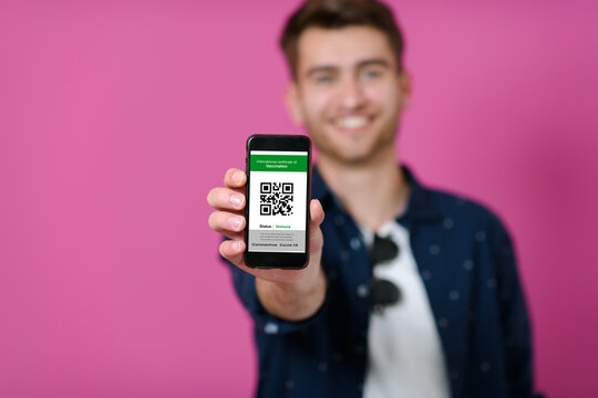 covid passport a young man shows his qr code and covid19 passport on his cell phone