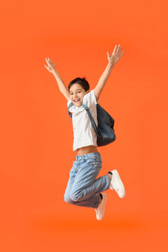 Jumping little schoolboy on color background