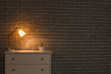 Chest of drawers with glowing lamp and houseplant near brick wall