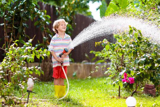 Boy watering flower in garden. Kid with water hose
