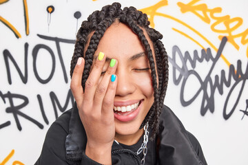 Close up shot of happy teenage girl makes face palm smiles broadly has colorful manicure and dreadlocks expresses positive emotions poses against drawn graffiti wall dressed in fashionable clothes