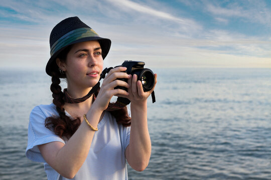 a girl with a camera looking at the subject, against the blue sea