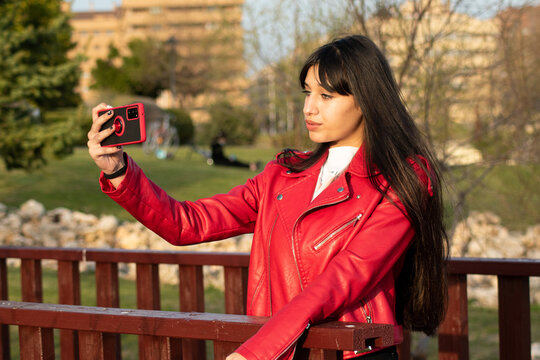 Green-eyed Latina teen taking a selfie with her mobile in the park with a red check