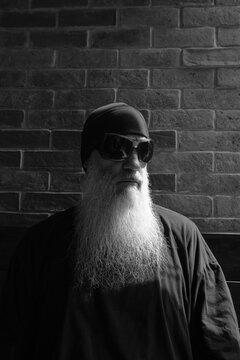 Black and white portrait of mature man with long gray beard thinking and wearing sunglasses and beanie