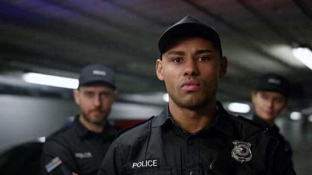 Policeman posing at camera. Police officer in cap standing at patrol car