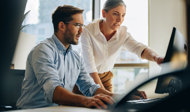 Businessman and woman working on computer together