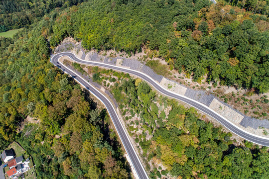Winding road serpentine from a high mountain pass in the rhine village Bendorf Sayn Germany Aerial view
