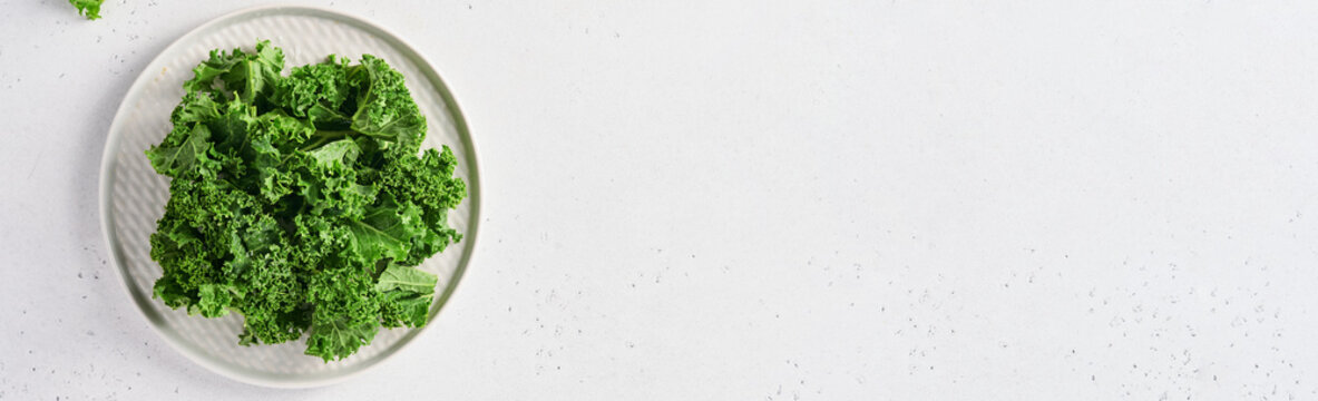 Bowl of fresh green chopped kale on light gray stone background, top view. Ingredient for making healthy salad. Clean eating, detox or diet concept. Mock up. Banner.