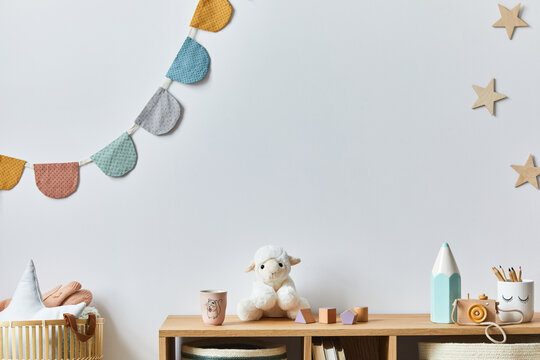 Stylish scandinavian newborn baby room with toys, plush animal, photo camera, doll and child accessories. Cozy decoration and hanging cotton balls on the white wall. Copy space.