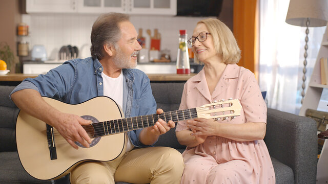 While the bearded old man plays the guitar, his wife gets rhythm with her hands and sings the song.Concept of having fun together, singing with guitar.