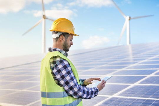 Man working at solar power station with digital tablet - Renewable energry with wind turbines and solar panels