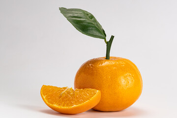 Fototapete - Side view of mandarin orange or Citrus reticulata a whole and a piece with leaf on white background with clipping path.