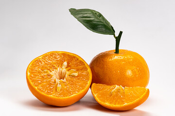 Fototapete - Side view of mandarin orange or Citrus reticulata a whole, a half and a piece with leaf on white background with clipping path