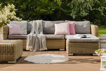 Obraz Pastel pink pillows on grey sofa in green garden with wooden terrace - fototapety do salonu