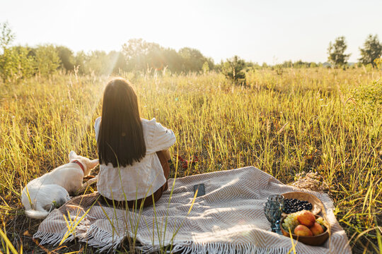Stylish woman sitting with her dog on yellow blanket in sunny light in summer meadow.  Picnic