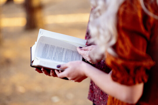 Closeup of women reading the bible in a park under the sunlight with a blurry background
