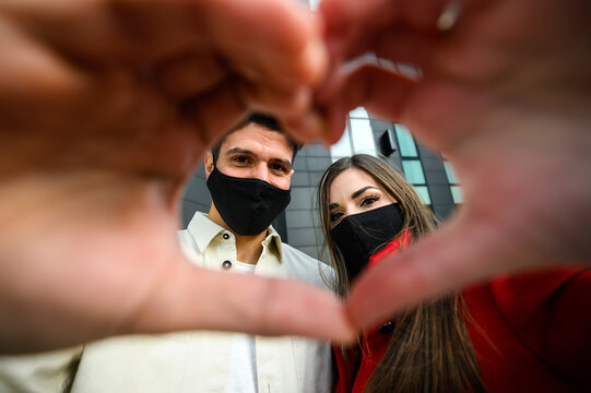 Couple wearing masks and making the sign of a heart, covid and coronavirus concept