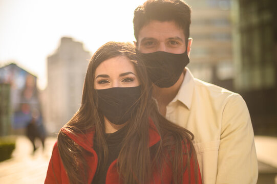 Romantic happy couple wearing masks against coronavirus covid 19 pandemic