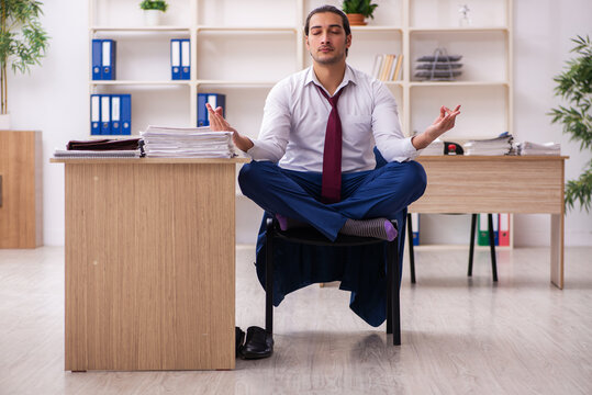 Young male employee doing yoga exercises during break