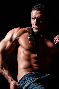Muscular model sports young man on dark background. Fashion portrait of strong brutal guy. Leather belt, jeans. Sexy torso. Sport workout bodybuilding concept. Sensual man's body