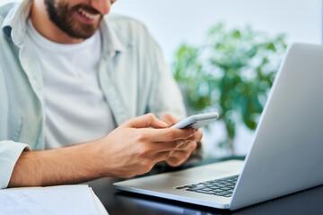 Fototapeta Closeup of happy man texting on mobile phone smartphone while using laptop obraz