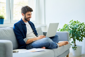 Young man study at home sitting on sofa using laptop