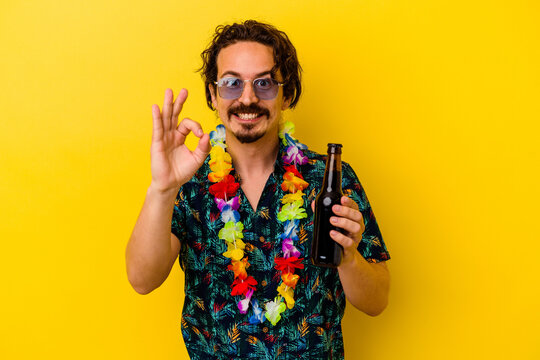 Young caucasian man wearing a hawaiian necklace holding a beer isolated on yellow background cheerful and confident showing ok gesture.