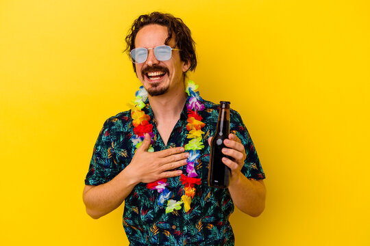 Young caucasian man wearing a hawaiian necklace holding a beer isolated on yellow background laughs out loudly keeping hand on chest.