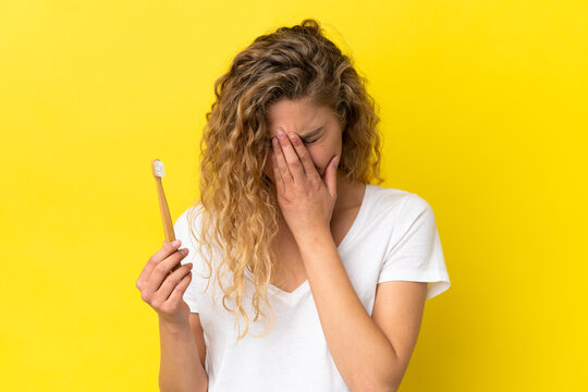 Young caucasian woman holding a brushing teeth isolated on yellow background with tired and sick expression