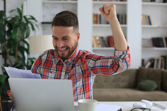 Handsome businessman is keeping arms raised and expressing joyful at home office.