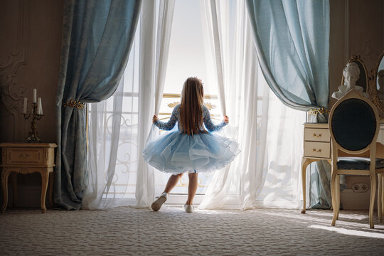 Back view of little girl in blue dance dress standing by the window, opening curtains in luxury apartment bedroom and looking out at the sea. Image with selective focus