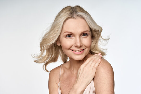 Happy smiling adult 50s aged woman looking at camera with hand on her shoulder portrait isolated on white background. Hair and skin anti age care products advertising concept.