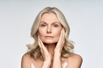 Obraz Adult senior older woman touching her perfect skin. Beautiful portrait mid 50s aged woman advertising facial anti age lift products salon care tighten skin isolated on white looking at camera. - fototapety do salonu