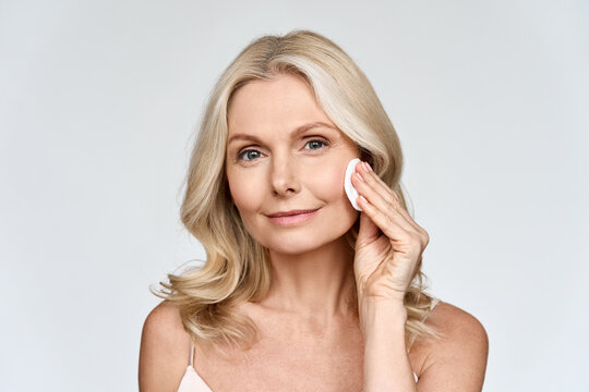 Portrait isolated on white of beautiful middle age 50 woman doing her everyday routine removing her makeup with cotton pad enjoying anti age healthy perfect products skin. Beauty and care advertising.