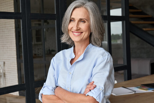 Smiling adult middle aged business woman standing at table posing in home office, arms crossed. Portrait of gray haired happy professional ceo or financial director woman in corporate photoshoot.