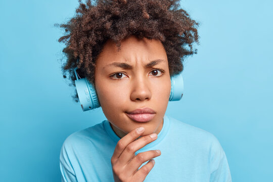 Close up portrait of serious Afro American girl keeps hand on chin looks displeased at camera dressed casually listens music via headphones or learns new foreign words isolated over blue background
