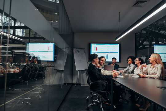 Group of successful smiling business people discussing work in a spacious conference office. Presentation. Data analysis, statistics, finance.Business team.Copy space.