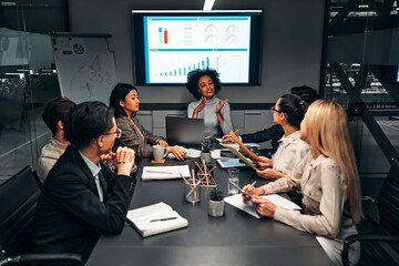 Young confident successful business people discuss and analyze work, statistics, plans, startup in a meeting room. Teamwork. Presentation.