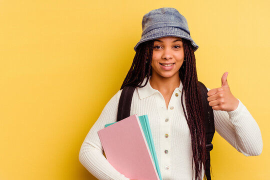 Young african american student woman isolated on yellow background smiling and raising thumb up