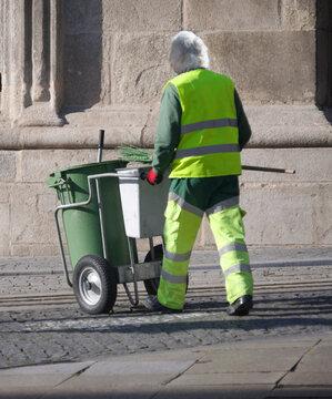 Varredor de rua com carrinho e uniforme de cores fluorescentes e refletoras - trabalho, profissão de limpeza de cidades