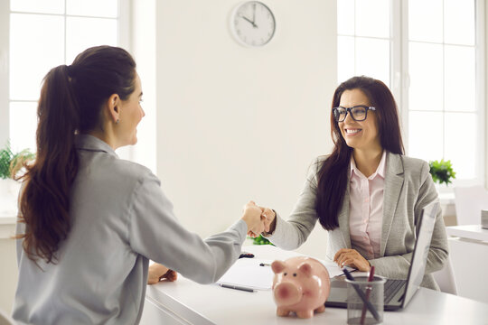 Female bank manager shakes hands with a client during a meeting to sign a financial investment agreement. Happy financial advisor greets his female client after signing the insurance contract.