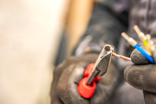 Electrician hands hold wire cutters and close-up of wires. The idea of repairing and connecting electrical wiring at home or at work